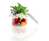 Caprese Salad in an Open Lid Jar. Fresh farm style caprese salad in an open lid mason jar isolated on white with reflexion royalty free stock image