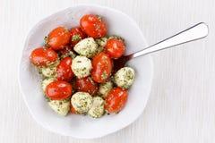 Caprese salad with pesto. Mozzarella cheese and cherry tomatoes with pesto sauce royalty free stock image