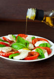 Caprese Salad With Pouring Olive Oil Royalty Free Stock Photos