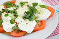 Caprese salad with rucola. Mediterranean recipe made with tomato, mozzarella, olive oil, oregano and more rocket Royalty Free Stock Photography