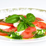 Caprese salad. Salad with mushrooms and bacon in sauce. Square crop. Tasty and beautiful Caprese salad on the plate Royalty Free Stock Photography
