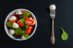 Caprese salad, small mozzarella cheese, fresh green leaves, black olives and cherry tomatoes in white vintage bowl on stone Stock Images