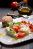 Caprese salad with tomatoes, basil,  mozzarella balls, made with. White ball mozzarella buffalo Italian soft cheese and olive oil Royalty Free Stock Image