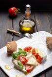 Caprese salad with tomatoes, basil,  mozzarella balls, made with. White ball mozzarella buffalo Italian soft cheese and olive oil Royalty Free Stock Photo