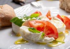 Caprese salad with tomatoes, basil,  mozzarella balls, made with. White ball mozzarella buffalo Italian soft cheese and olive oil Stock Photos