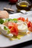 Caprese salad with tomatoes, basil,  mozzarella balls, made with. White ball mozzarella buffalo Italian soft cheese and olive oil Royalty Free Stock Photos