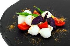 Caprese salad of tomatoes, basil, mozzarella, pepper. Studio Photo Royalty Free Stock Photos