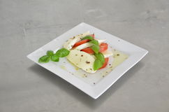Caprese salad with tomatoes, basil and mozzarella on the table of stainless steel Stock Photos