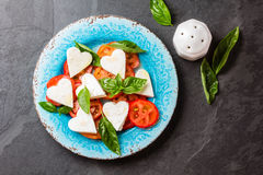 Caprese salad with tomatoes, cheese hearts, basil. Valentine day menu Stock Photos