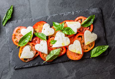Caprese salad with tomatoes, cheese hearts, basil. Valentine day menu Royalty Free Stock Photography