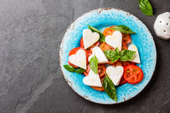 Caprese salad with tomatoes, cheese hearts, basil. Valentine day menu Stock Image