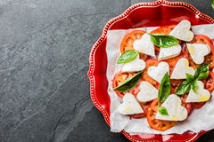 Caprese salad with tomatoes, cheese hearts, basil. Valentine day menu Stock Photography