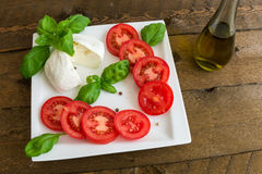 Caprese salad with tomatoes and mozzarella on the plate Stock Photo