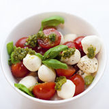 Caprese salad. In white deep plate with pesto sauce Royalty Free Stock Photo