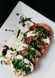 Caprese Salad on a white plate with dark background Royalty Free Stock Images
