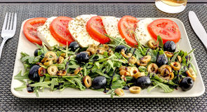 Caprese salad on white plate. Italian cuisine. Mediterranean cuisine. Tomatoes, mozzarella, basil leaves and olive oil on wooden t Royalty Free Stock Photos