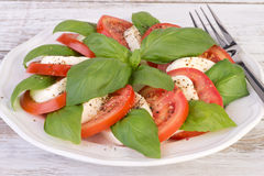 Caprese salad on wooden table stock photography