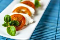 Caprese-Salat mit blauer Matte stockbilder