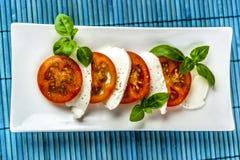 Caprese-Salat mit blauer Matte von oben stockfotos