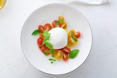 Caprese-Salat mit den roten und gelben Tomaten, mozarella, Basilikum und Olivenöl Nahe Ansicht Draufsicht des weißen Hintergrunde Stockbild