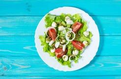 caprese sallad Körsbär-tomater behandla som ett barn spenat och mozzarellaen i metallbunke med pestodressingen på den lantliga tr Royaltyfria Bilder