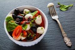 Caprese sallad, liten mozzarellaost, nya gräsplansidor, svarta oliv och körsbärsröda tomater i vit tappning bowlar på stenbackgr Arkivbilder
