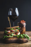 Caprese sandwich, glass of wine and dried tomatoes in jar Stock Photography