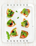 Caprese sandwiches with tomato, mozzarella cheese, basil and balsamic glaze on white baking tray over light wooden Stock Photo