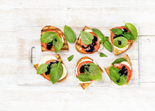 Caprese sandwiches with tomato, mozzarella cheese, basil and balsamic glaze on white painted wooden background Stock Images