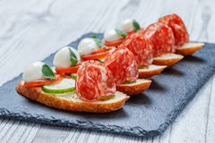 Caprese sandwiches with tomato, mozzarella cheese, basil, salami on ciabatta bread on stone slate background close up. Stock Image