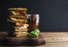 Caprese smörgås eller panini Helt kornbröd, mozzarella, körsbär och torkade tomater, basilika Arkivfoto