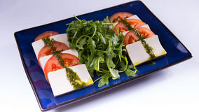 Caprese with tofu on blue chinese plate on white background stock photos