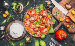 Caprese tomatoes mozzarella salad  on dark rustic background with oil, balsamic vinegar, cutting board and ingredients Royalty Free Stock Image