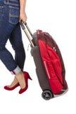 佩带Capri蓝色牛仔裤和绒面革红色泵浦的妇女拉扯一件小旅行行李 库存照片
