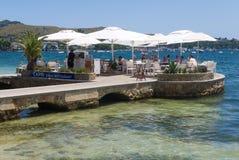 Capri Bar in Mallorca, Spain. Mallorca, Spain - July 7, 2017: Patrons enjoy a seaside view as they eat at the Capri Bar & Restaurant in Port de Pollenca Royalty Free Stock Photos