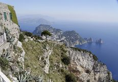 Capri and the Faraglioni. The group of stone Islands named Faraglioni on the shore of the Capri Island and the housing over the hill of Capri itself. Some boats stock images