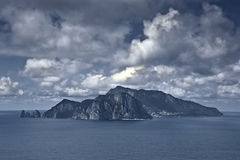 Capri Island clouds seascape. Gloomy island Capri is visible on the horizon Stock Photography