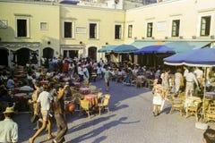 CAPRI, ITÁLIA, 1965 - o sol ajusta-se nas mesas de centro e em transeuntes no Piazzetta famoso de Capri fotos de stock