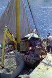 CAPRI, ITÁLIA, 1974 - os trabalhadores descarregam tijolos e materiais de construção de um navio de carga na doca do porto imagem de stock royalty free