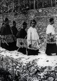 Capri, Italië, 1929 - Één of andere godsdienstige parade in soutane met kaarsen tijdens de vieringen van San Costanzo, patroon va stock foto