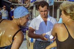 CAPRI, ITALIË, 1967 - Twee atleten ruilt een grap onder de nieuwsgierige starende blik van een medewerker, bij het begin van het stock foto's