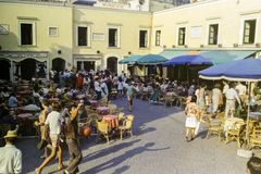 CAPRI, ITALIA, 1965 - il sole mette sui tavolini da salotto e sui passanti nel Piazzetta famoso di Capri fotografie stock