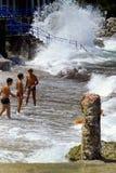 CAPRI, ITALIA, JULIO DE 1969 - tres muchachos desafían las ondas durante una inflamación entre los guijarros, las rocas y una col fotos de archivo libres de regalías