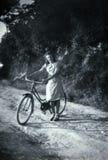 Capri Italien, 1932 - en flicka ler glatt med hennes cykel royaltyfri foto