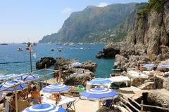 CAPRI, ITALIEN - 4. JULI 2018: felsiger Strand zwischen Faraglioni-Klippen von Capri, Italien stockfotografie