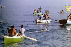 CAPRI ITALIEN, 1967 - några idrottsman nen simmar i golfen av Naples i det traditionella loppet för Capri-Naples maratonlängdl royaltyfria bilder