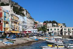 Busy beach with boats docked and people walking in the island of. Capri, Italy 2015-06-27 Busy beach with boats docked and people walking in the island of Capri royalty free stock photography