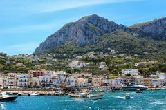 Busy beach with boats docked and people walking in the island of. Capri, Italy 2015-06-27 Busy beach with boats docked and people walking in the island of Capri royalty free stock photos