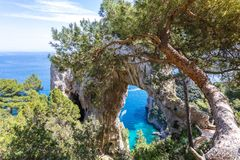Capri Italy, island in a beautiful summer day, with faraglioni rocks and natural stone arch. Beautiful panoramic view and trees surrounding the geologic Royalty Free Stock Images
