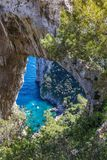 Capri Italy, island in a beautiful summer day, with faraglioni rocks and natural stone arch. Close-up of the stone arc, with little turquoise bay and some Royalty Free Stock Photography